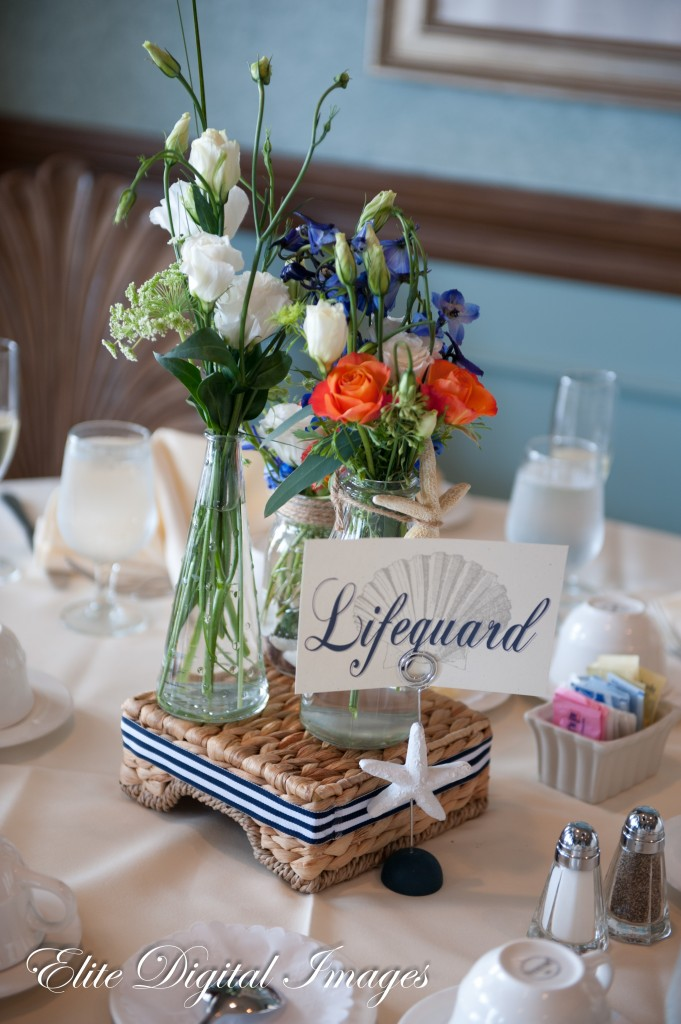 Kim and Jon kept it very simple for their beach themed wedding. Small vessels filled with colorful flowers on top of woven napkin holders rimmed with ribbon and seashells. Photo courtesy of Elite Images.