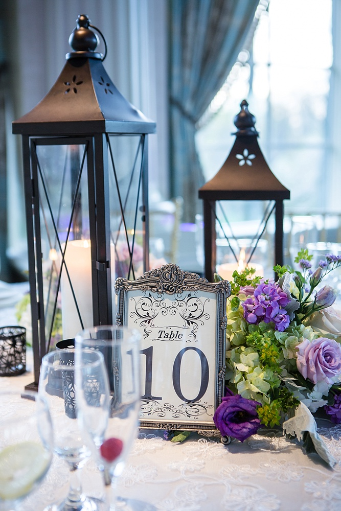 Dana and Cyril's wedding featured two different centerpieces. Shown here are the lanterns interspersed with lavendar and green flowers. The second arrangement featured thick pillar candles on various height pedestals also interspersed with flowers. Photo courtesy of The Artist Group.